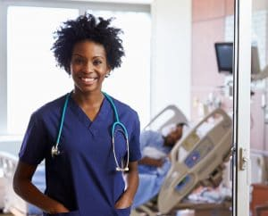 black female doctor with stethoscope in hospital patient room
